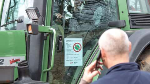 Hinweisschild zur Eindämmung der Ausbreitung des Corona-Virus an einem Traktor